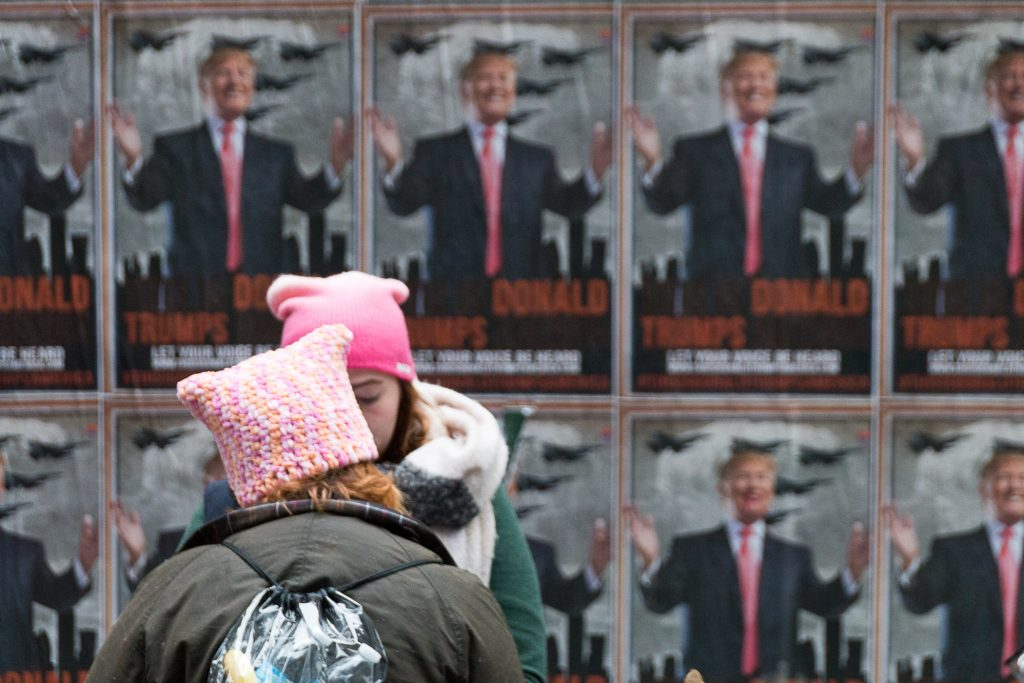 Young women in pink pussy hats prepare for the New York City Womens March in front of a wall of Donald Trump signs
