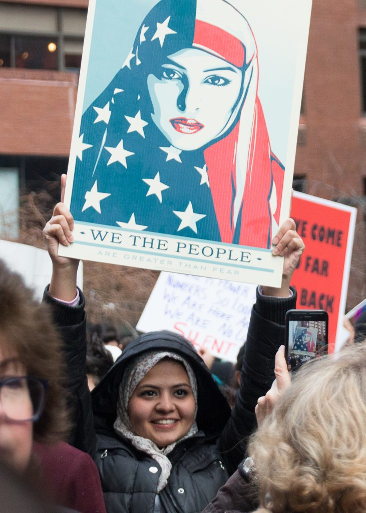 "A young woman in a headscarf at the New York City Women's March holds up Shepard Fairey's ""WE THE PEOPLE"" poster featuring a woman in an American flag headscarf."