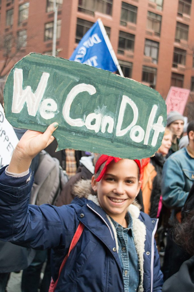 "A young woman, dressed in costume as the famous ""We Can Do It!"" poster at the New York City Women's March"