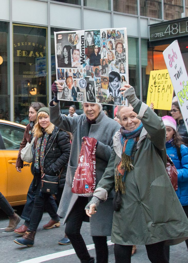 Two women at the New York City Women's March, holding a handmade collage featuring images of famous and notable women.