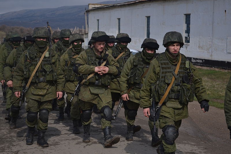Russian soldiers, bearing no official markings, guarding a seized Ukrainian base in Crimea in March of 2014. Image via Wikimedia.