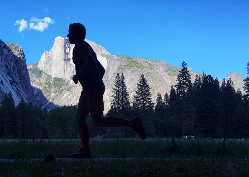 Running, silhouetted against the backdrop of Half Dome in Yosemite National Park.